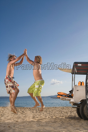 young men at beach jump by