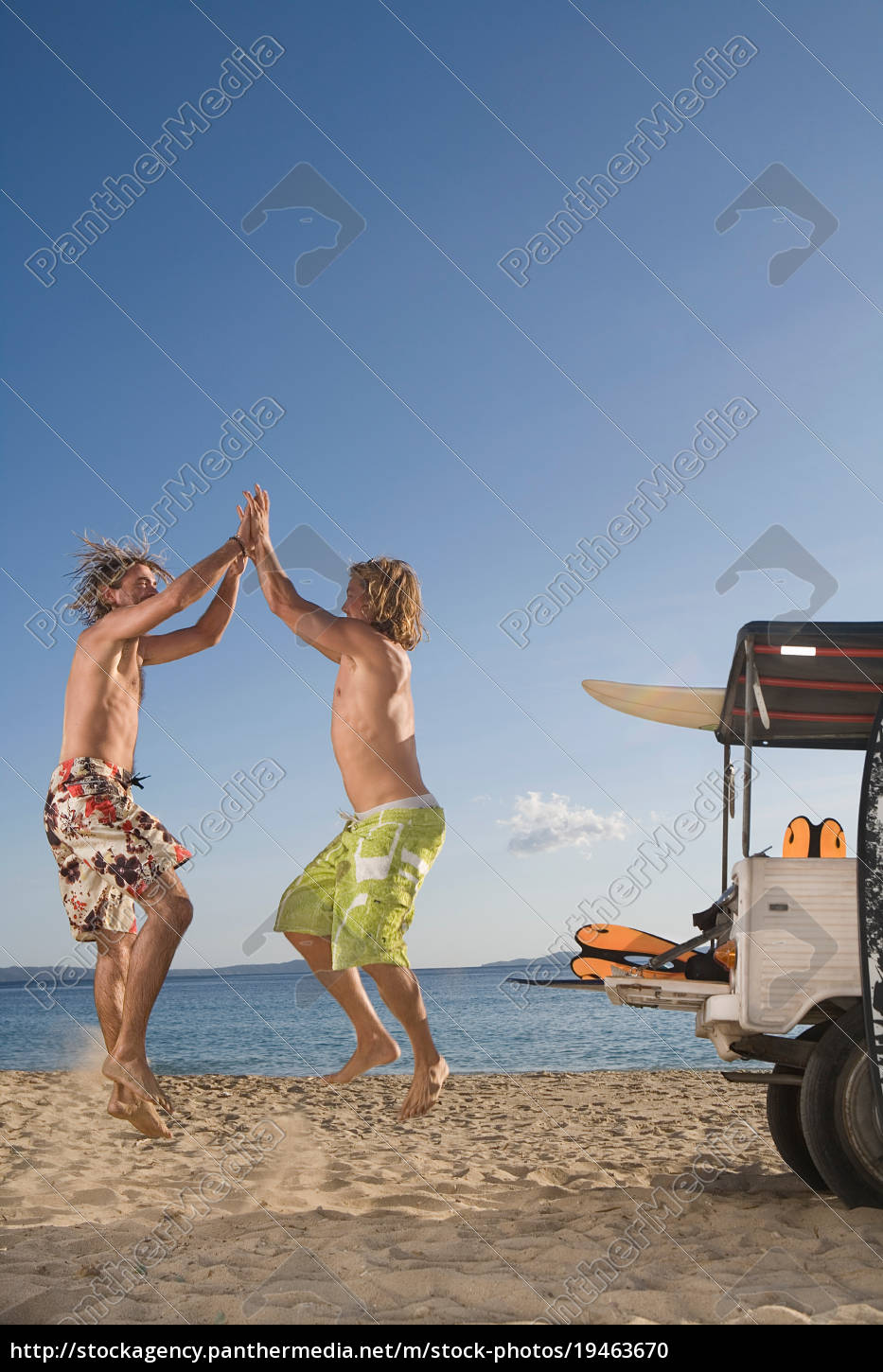 young, men, at, beach, jump, by - 19463670