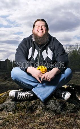 happy bearded man sitting in field