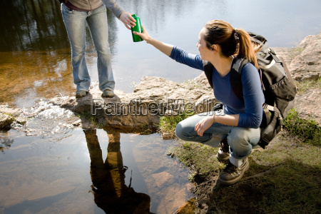 two women with water beside lake