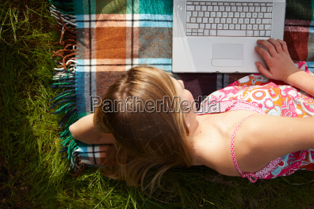 woman lying on blanket using laptop
