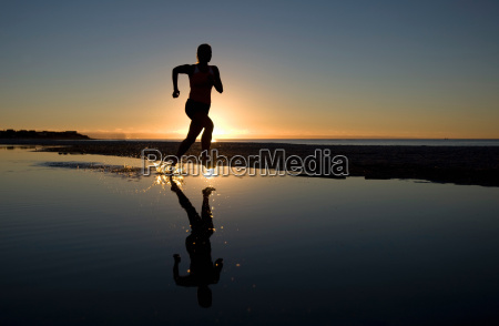 young woman running on beach at