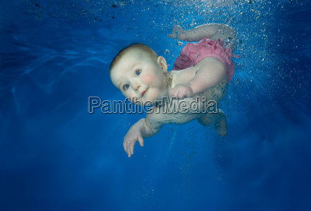 female baby swimming underwater