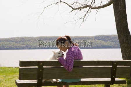 woman with dog on park bench