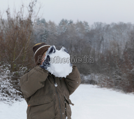 boy hiding face behind snowball