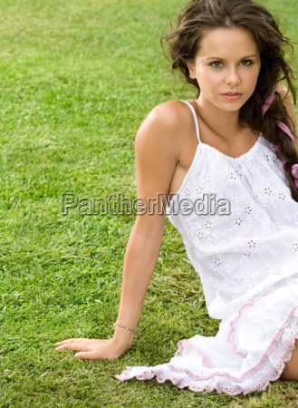 woman sits in grass