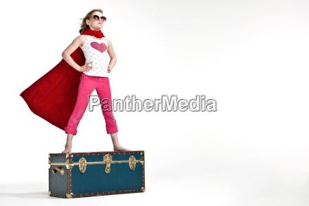 girl standing on trunk suitcase dressed