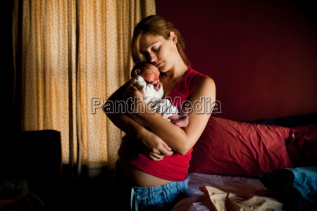 mother embracing newborn baby son