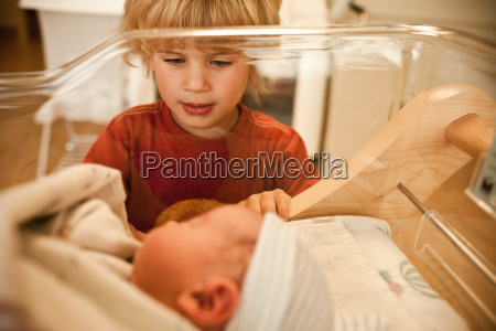boy looking at newborn baby brother