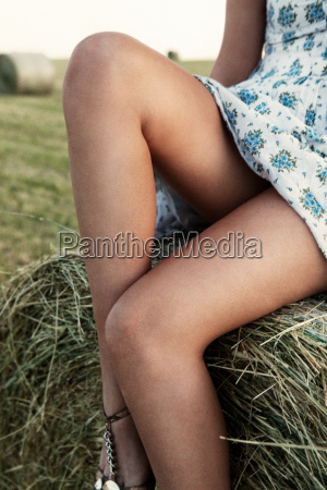 young woman sitting on hay bale