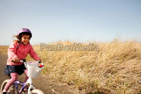 young girl cycling along lane
