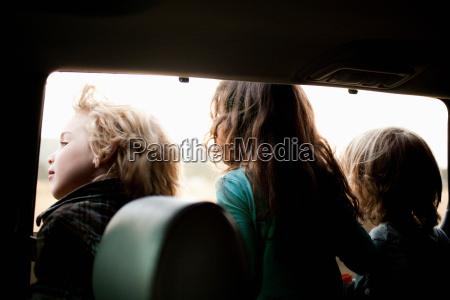 three children looking through car window