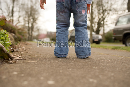 young girl standing on pavement