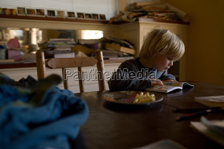 young boy sitting at kitchen table