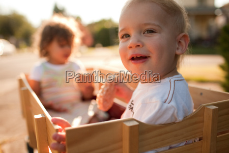 two children sitting in wooden wagon