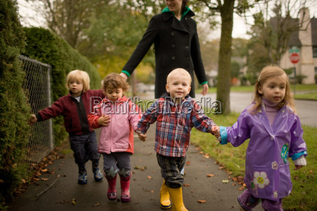 woman with four children walking along