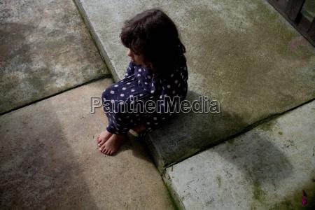 young girl sitting on sidewalk