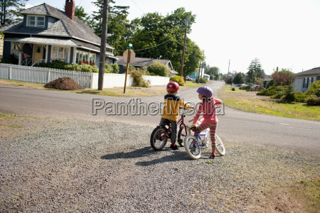 brother and sister on bicycles in