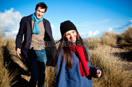 couple strolling in sand dunes bournemouth