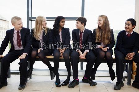 group of teenage schoolchildren sitting in