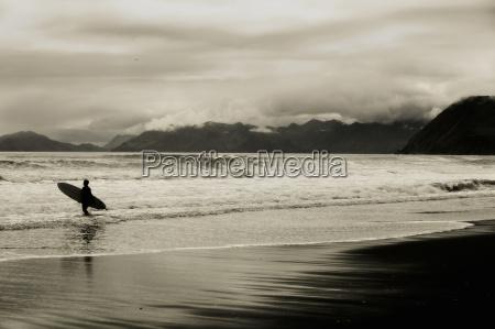 surfer on beach kodiak alaska usa
