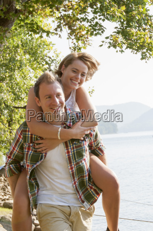 young man giving woman piggy back