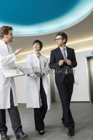 three mid adults walking through lobby