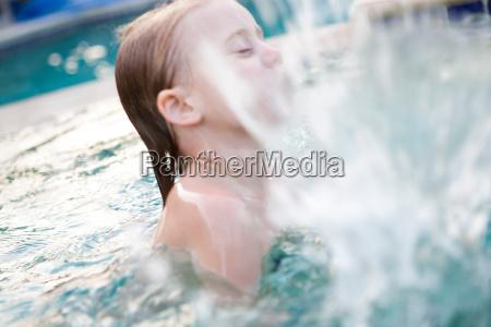 little girl splashing in swimming pool