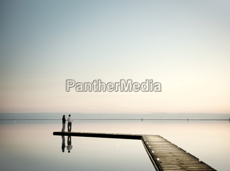 mature couple standing on jetty overlooking
