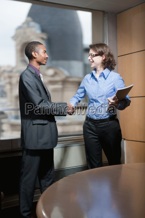 man woman shaking hands in office