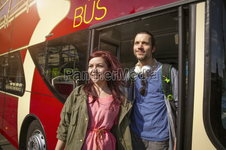 young adult couple getting off bus