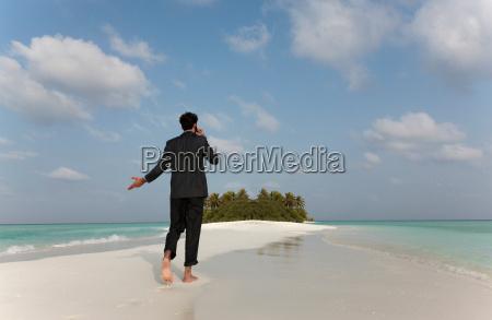 businessman on cell phone on beach