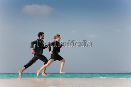 business people running on beach