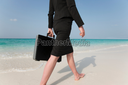 businesswoman walking on tropical beach