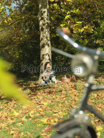 woman with picnic under tree in