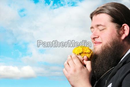 bearded man smelling flowers