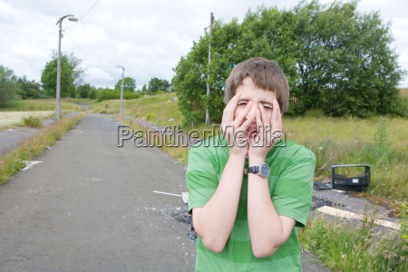 teenage boy covering face with hands
