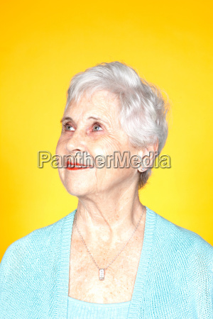 senior woman looking up studio shot