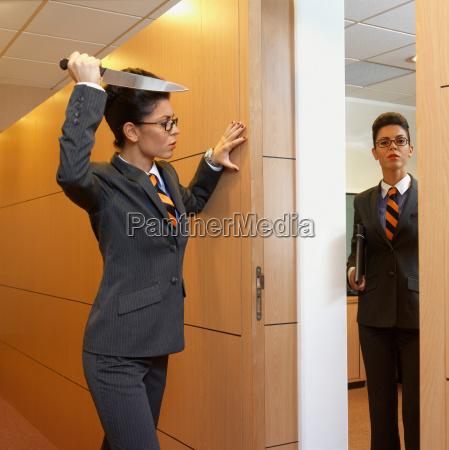 geschaeftsfrau haelt ein messer