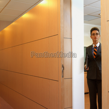 businesswoman coming out of her office