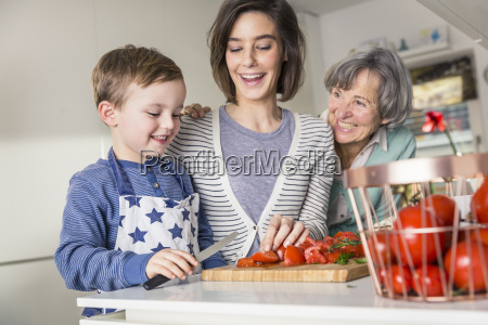 mother and grandmother helping boy slice