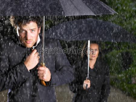 mann und frau mit sonnenschirmen regnet