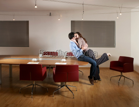 man and woman kissing in office