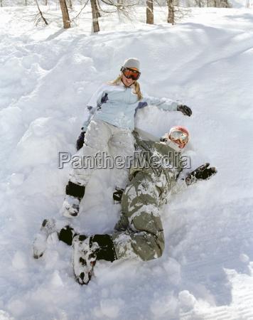 paare die im schnee sitzen lachen
