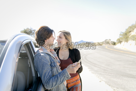 young couple leaning against car holding