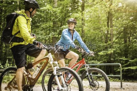 mature mountain biking couple chatting and