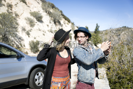 young couple wearing hats using smartphone