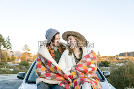 young couple on car bonnet wrapped