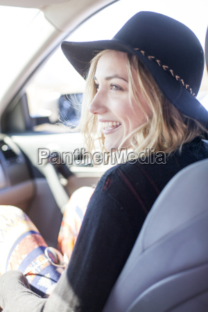 young blonde woman sitting in car