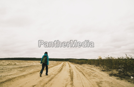 young woman hiking along dirt road